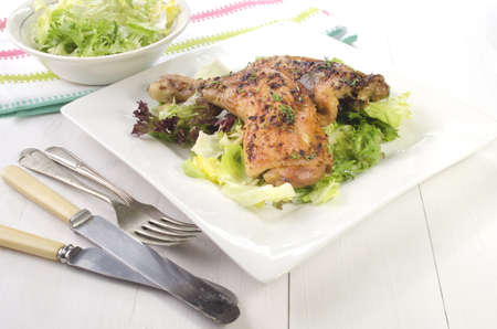 oven chicken: oven baked thyme chicken drumsticks on fresh green salad Stock Photo