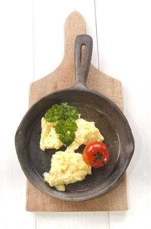 cast iron red: scrambled eggs, roasted tomato and parsley in an cast iron pan