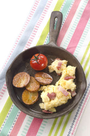 cast iron: roasted potato with scrambled egg, grilled bacon and tomato in a cast iron pan
