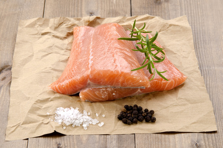 fresh meat: fresh salmon fillet with rosemary, coarse salt and pepper corn on brown paper Stock Photo