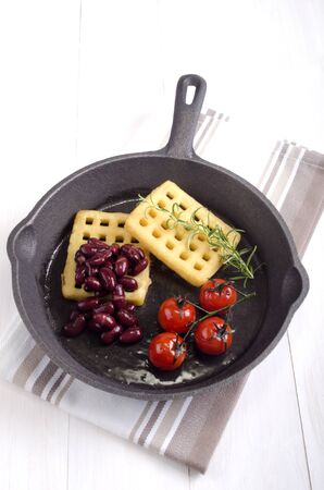 cast iron pan: cast iron pan with potato waffle, tomato and kidney beans