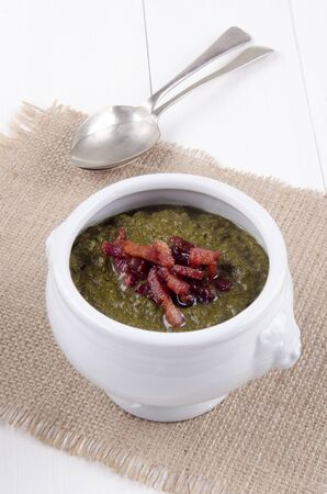 bacon bits: callaloo soup with grilled bacon bits in a white bowl