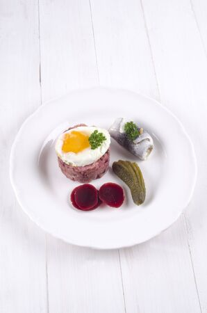 gherkin: labskaus with fried egg, pickled herring, beetroot, gherkin and parsley on a white plate Stock Photo