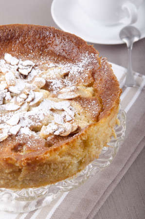 sliver: apple cake with almond sliver and powdered sugar on a cake stand