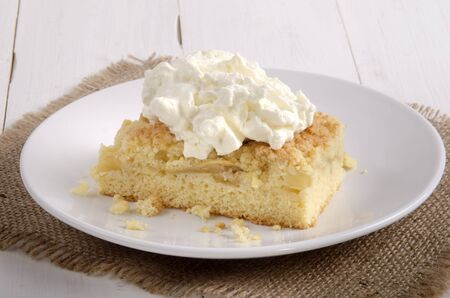 whipped cream: apple crumble cake with whipped cream on a plate Stock Photo