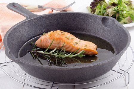 cast iron pan: grilled salmon fillet with thyme, rosemary and olive oil in a cast iron pan