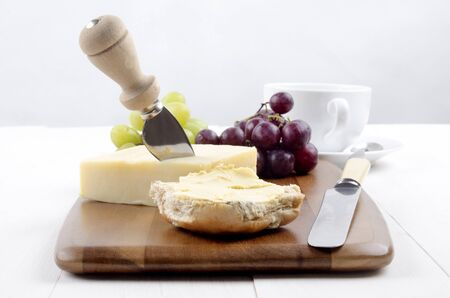 cheese knife: irish cheddar cheese with a cheese knife, half of buttered bun, cup of coffee and grapes on wooden board