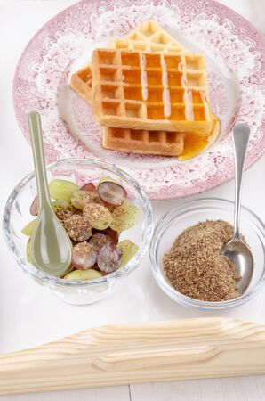 milled: breakfast on a serving tray with grape, waffle, honey, spoon and milled flaxseed