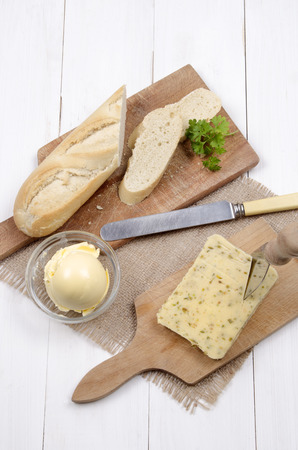 cheese knife: cheese with jalapeno chili and baguette, margarine and parsley with cheese knife on wooden board