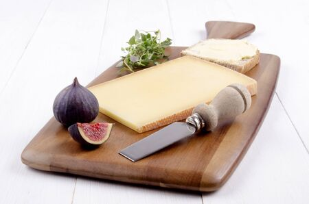 cheese knife: Swiss hard cheese, fresh thyme, fig, cheese knife and bread with butter on a brown wooden board