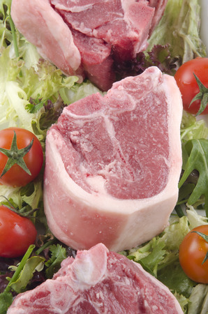 lamb chop: raw lamb chop with tomato and salad on a plate Stock Photo