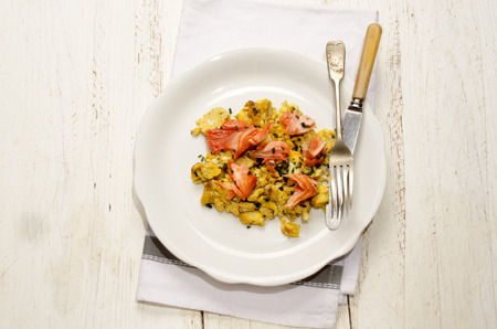 peces: scrambled eggs with salmon and dill on a white plate Foto de archivo