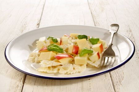 fruity salad: fruity noodle salad with mayonnaise, cheese, basil and red apple cube Stock Photo
