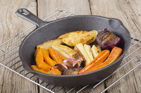 cast iron pan: grilled carrot, lilac onion, turnip with oil in a cast iron pan Stock Photo