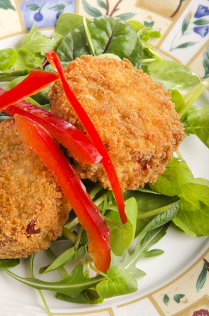 fresh food fish cake: salmon fish cake with red bell pepper stripes on fresh green salad
