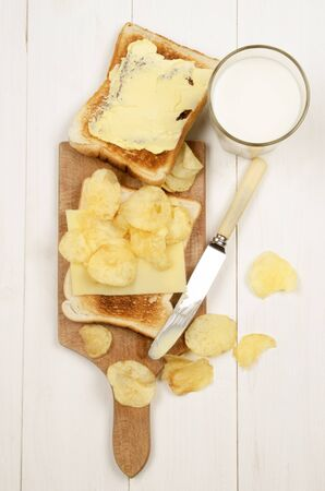 mild: toast bread with a slice of mild irish cheddar, salted crisps and a glass of fresh milk Stock Photo