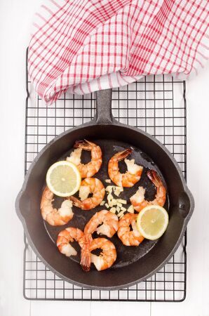 cast iron pan: grilled king prawns with lemon slice and crushed garlic in a cast iron pan