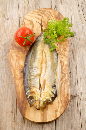 kipper: kipper with fresh tomato and parsley on wooden board