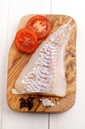 whitefish: haddock fillet with tomato, pepper and coarse salt on a wooden board