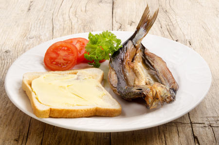 kipper: grilled kipper with bread, tomato and parsley on a plate Stock Photo