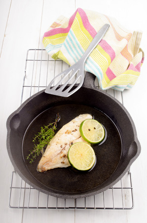 cast iron pan: grilled river cobbler with lime slice in a cast iron pan Stock Photo