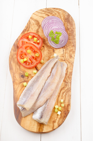 seafish: herring with tomato, lilac onion, parsley and spring onion on a wooden board