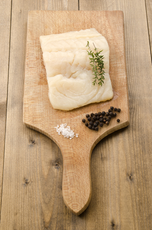 haddock fillet with thyme, coarse salt and pepper on a wooden board