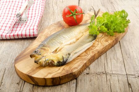 kipper: smoked kipper with tomato and parsley on a wooden board