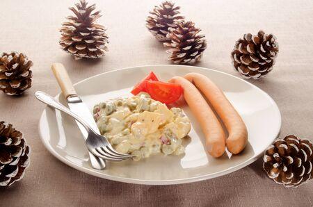 salad decoration: potato salad, vienna sausage, tomato on a plate and pine cone as christmas decoration Stock Photo