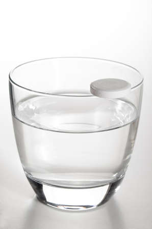 vitamin pill: glass filled with cold water and a vitamin pill