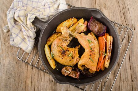 cast iron pan: grilled chicken drumsticks with garlic, carrot, parsnip and lilac onion in a cast iron pan Stock Photo