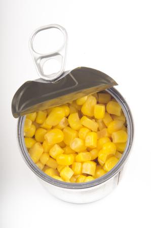 vegetable tin: open metallic tin with sweet corn on white background