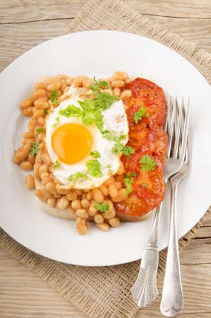 beans on toast: fried egg with grilled tomato slices, baked beans, parsley and toast bread on a plate Stock Photo