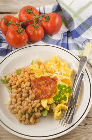 beans on toast: scrambled eggs with grilled tomato and baked beans on toast bread