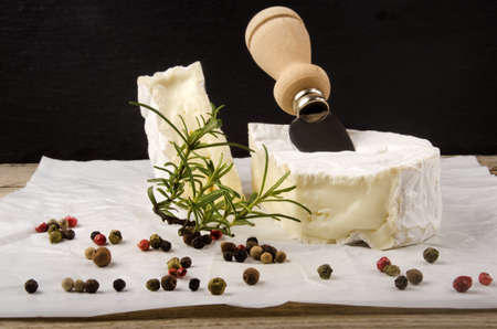 cheese knife: camembert with cheese knife and colored pepper on white paper