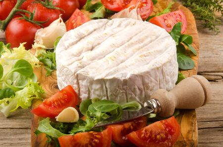 cheese knife: camembert with salad, tomato, garlic, thyme and cheese knife on wooden board