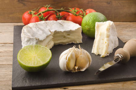 cheese knife: camembert with lime, garlic, tomato and cheese knife on slate