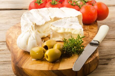 olive green: camembert with green olive, tomato, garlic and thyme on a wooden board