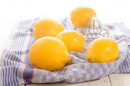 separator: organic lemons and lemon squeezer on a kitchen towel