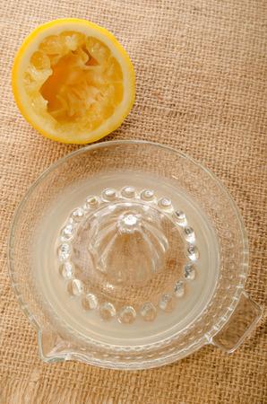 juice squeezer: squeezed lemon, glass lemon squeezer and fresh lemon juice on jute