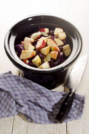slow cooker: red cabbage with apple and bay leaf in a black slow cooker pot
