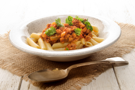 minced meat: penne rigate with tomato sauce, minced meat and parsley Stock Photo