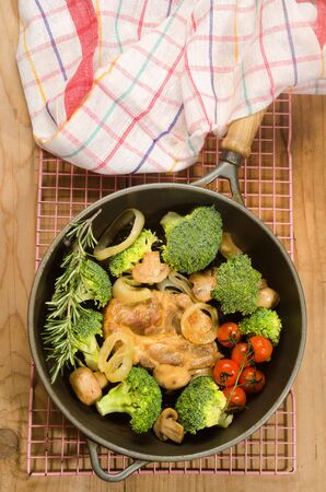 cast iron red: pork neck steak in a cast iron pan with broccoli, onion, mushroom, cherry tomato and rosemary