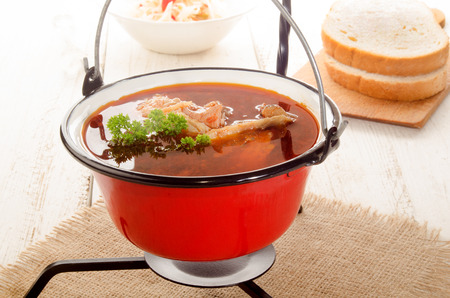 soup kettle: hungarian carp soup in a small red kettle and sour salad