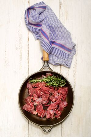 cast iron red: raw deer goulash with rosemary, pepper corn and coarse salt in a cast iron pan on white wood