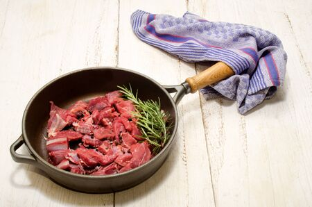cast iron pan: raw deer goulash with rosemary, pepper corn and coarse salt in a cast iron pan on white wood