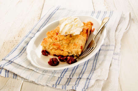 cherry crumble with whipped cream and fork on oval plate Stock Photo