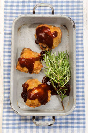 roasting pan: chicken thigh with barbecue sauce in rustic grey roasting pan Stock Photo