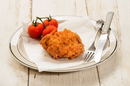 muslos: fried chicken thighs coated with corn flakes on kitchen paper and plate Foto de archivo