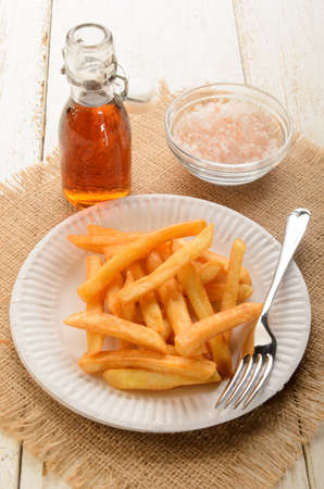 french fries plate: french fries on a white paper plate and malt vinegar